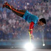 Ein Artist balanciert bei der Eröffnungsfeier auf Krücken.
