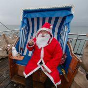 Was dieser Weihnachtsmann am Ostseestrand wohl vom Wetter hält? Und hat er gleich Sandäcke vor der Sturmfluten mitgebracht?