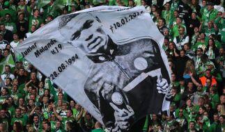Wolfsburgs Fans schwenken eine Fahne mit dem Konterfei des tödlich verunglücktem Junior Malanda. (Foto)