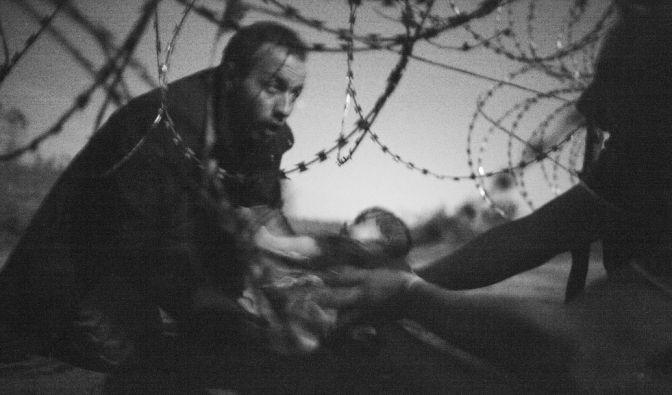 World Press Photo 2015: Das Bild zeigt einen Flüchtling der sein Baby durch einen Grenzzaun hält. (Foto)