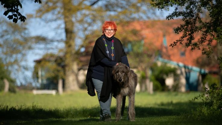 Barbara Salesch steht mit ihrem Hund Piri im Garten ihres Hauses in Petershagen.