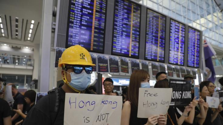 Demonstranten stehen am Flughafen von Hongkong.