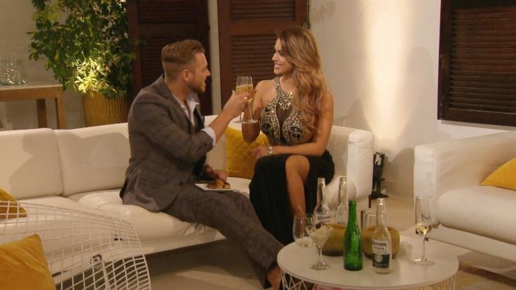 Bei einem Drink lernen sich Alex und Jessica besser kennen.