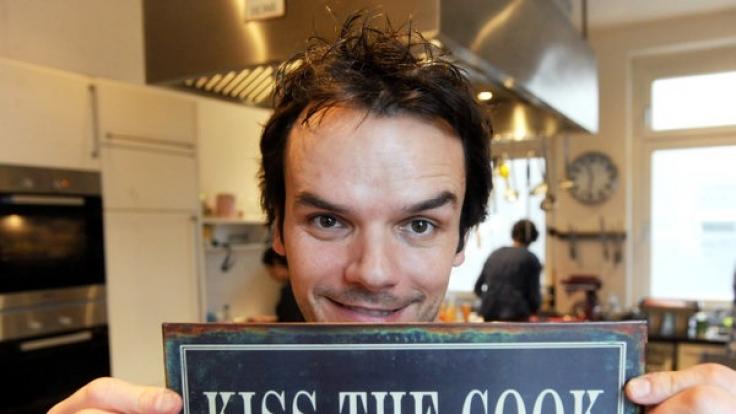 """Fernseh-Koch Steffen Henssler bei der Präsentation seines neuen Kochbuchs """"Hauptsache lecker!"""" mit einem Schild mit der Aufschrift """"Kiss The Cook"""". (Foto)"""