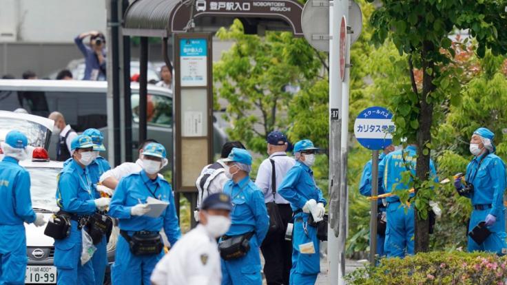 Ermittler sind neben einer Bushaltestelle für den Bus der CARITAS Grundschule am Tatort in Kawasaki im Einsatz.