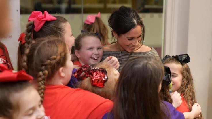 Stürmische Begrüßung: Meghan Markle wird von Kindern umarmt bei ihrem gemeinsamen Besuch mit Prinz Harry in Wales.