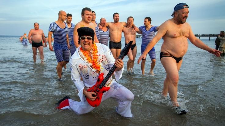 Mit einem Elvis-Kostüm wagt dieser Mann sich ins kühle Nass. (Foto)