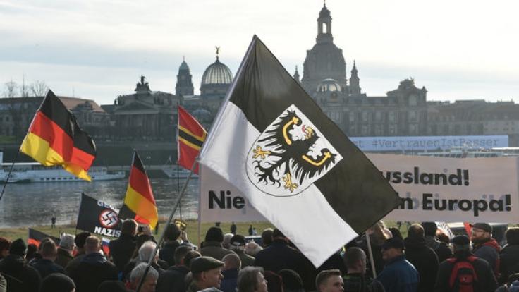 Teilnehmer einer Pegida-Demonstration in Dresden mit Deutschlandflaggen und einer Ostpreußen Fahne.
