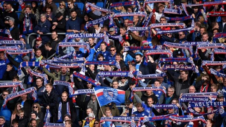 Von der Zuschauertribüne aus, unterstützen die Fans von Holstein Kiel ihren Verein. (Symbolbild) (Foto)