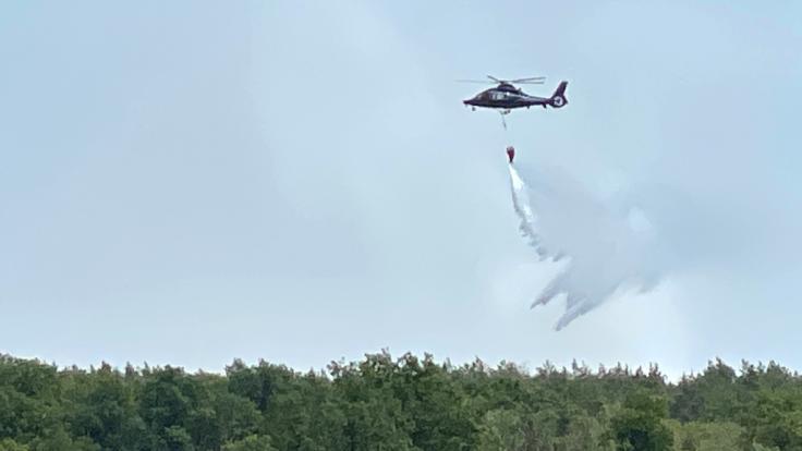 Ein Löschhubschrauber wirft Wasser über einem brennenden Waldstück nordwestlich von Berlin ab. (Foto)