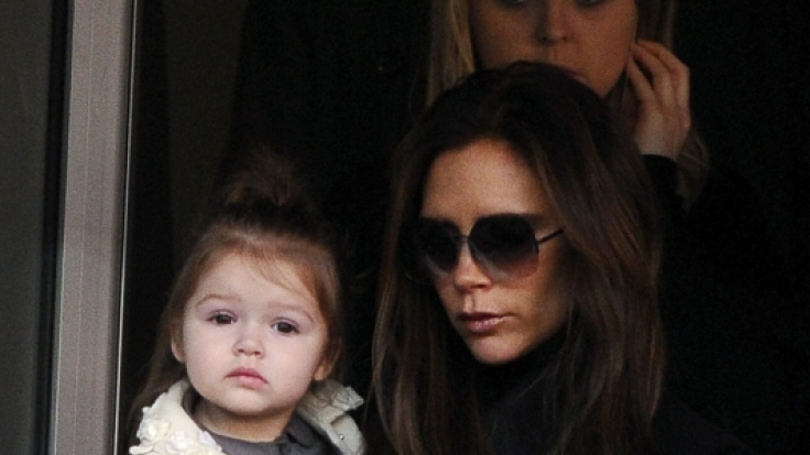 Harper Beckham auf dem Arm ihrer Mama Victoria Beckham - modisch wie immer.