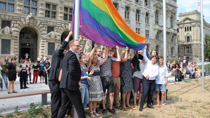 Leipzigs BürgermeisterUlrich Hörning (vorn) hisst mit CSD-Verantwortlichen die Regenbogenflagge. (Foto)