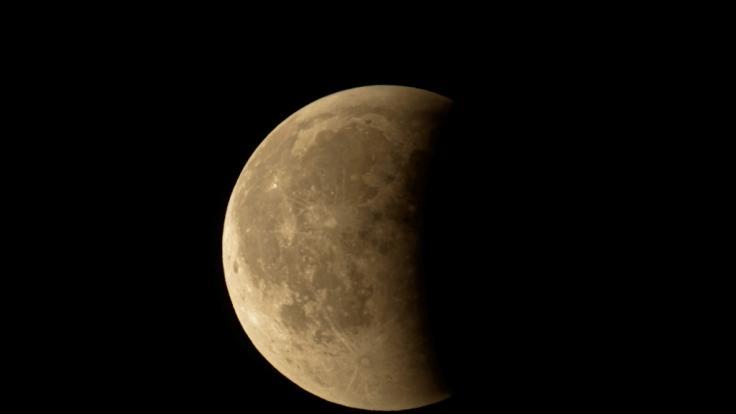 Eine partielle Mondfinsternis färbt den Donnermond rostrot.