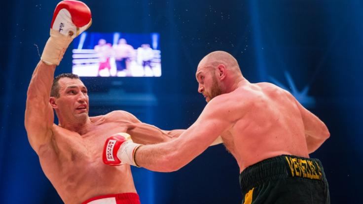 Der ukrainische Boxer Wladimir Klitschko (l), Weltmeister im Schwergewicht der WBA, WBO, IBO und IBF, und sein britischer Herausforderer Tyson Fury stehen sich am 28.11.2015 im Boxring gegenüber.