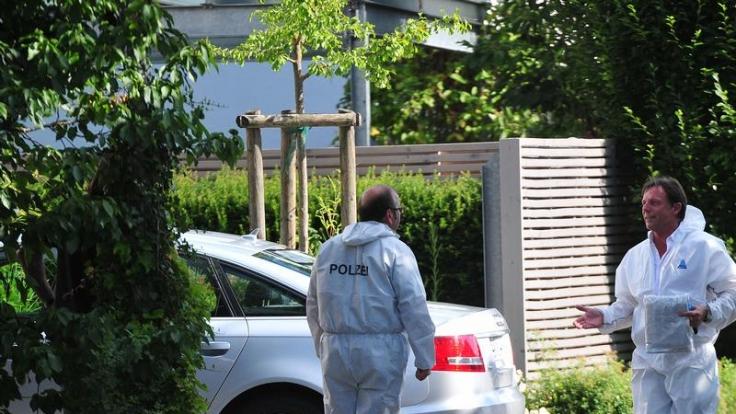 Kriminalbeamte in weißen Overalls sichern am Auto von Thomas Bögerl Spuren.