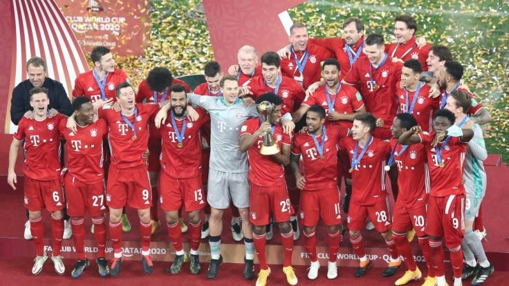 Die Spieler des FC Bayern München feiern mit der Trophäe. (Foto)