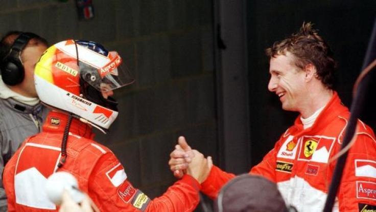 Michael Schumacher jubelt nach seinem Sieg mit seinem Teamkollegen Eddie Irvine, der Dritter wird.