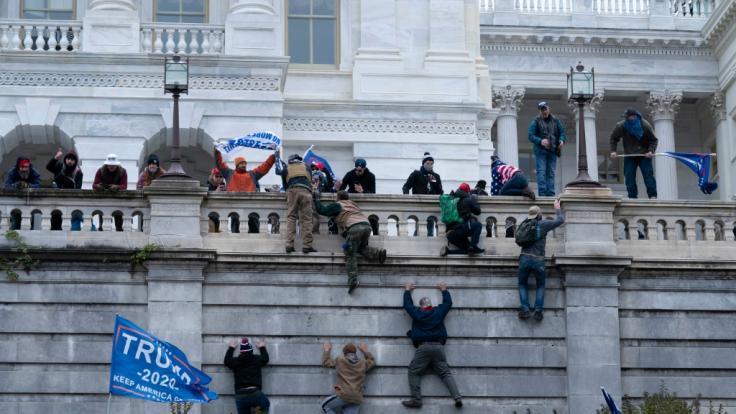 Anhänger von Präsident Donald Trump klettern in Washington auf die Westwand des US-Kapitols. (Foto)