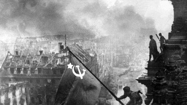 Der sowjetische Soldat Militon Kantarija hisst die sowjetische Flagge auf dem Berliner Reichstag.