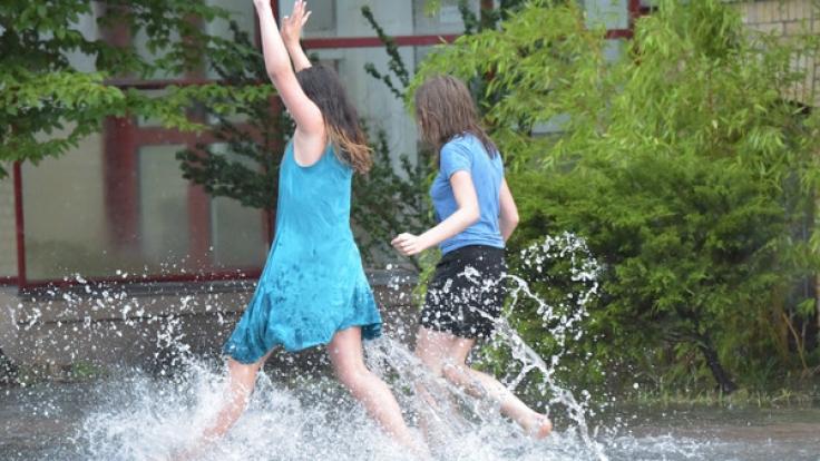 Zwei junge Frauen springen am 22.07.2017 durch vom Regen überschwemmte Wege in Hennigsdorf (Brandenburg).