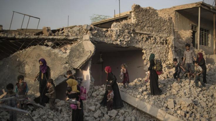 Menschen flüchten in der Altstadt von Mossul (Irak) durch die Trümmer.