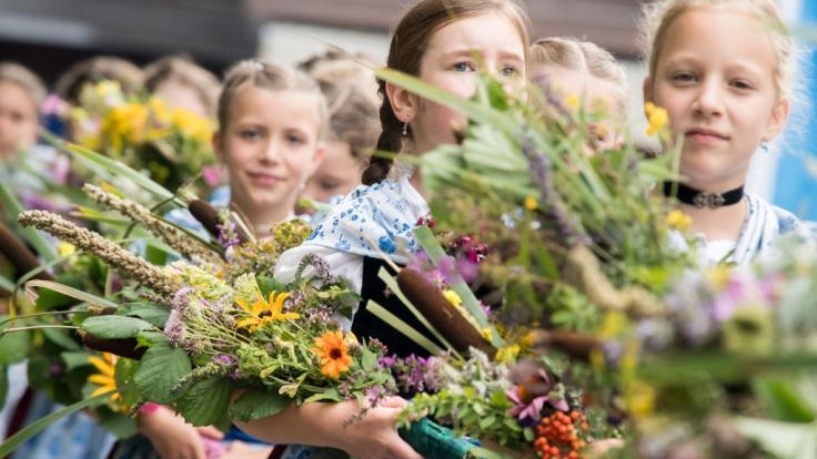 In Tracht gekleidete Mädchen tragen zu Maria Himmelfahrt in Kochel am See (Bayern) Kräuterbuschen in die Kirche. Alljährlich findet am 15. August der große Kocheler Heimattag statt.