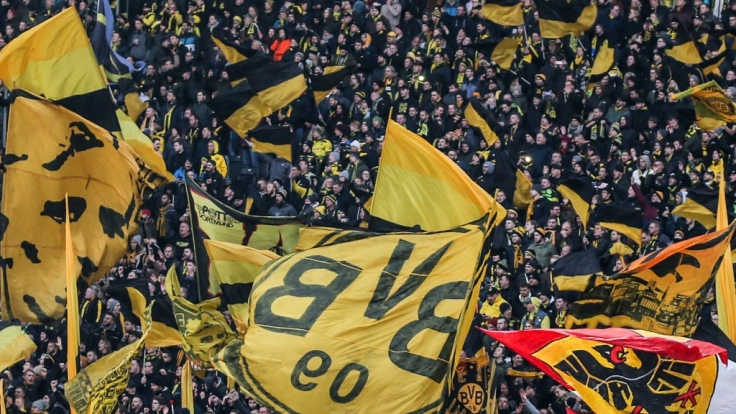 Mit wehenden Fahnen stehen die Fans des BVB hinter ihrer Mannschaft. (Symbolbild)