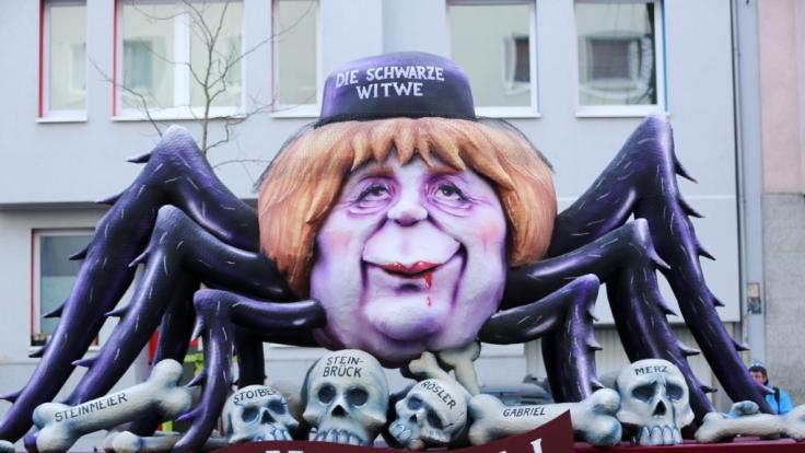 """Ein politischer Mottowagen mit der Figur der """"Bundeskanzlerin Angela Merkel, CDU als Schwarze Witwe"""" nimmt an dem Rosenmontagszug teil. (Foto)"""