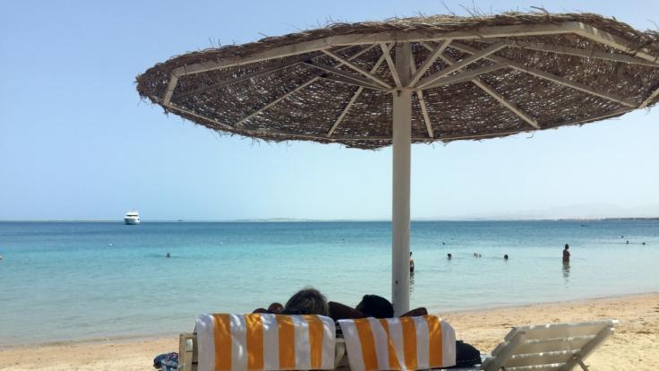 Eine Frau und ein Mann entspannen in Liegestühlen unter einem Sonnenschirm an einem öffentlichen Strand im ägyptischen Hurghada. Vor wenigen Tagen wurden in dem beliebten Urlaubsort zwei tote Hotelgäste aufgefunden.