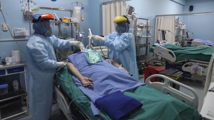 Mitarbeiter des Gesundheitswesens behandeln einen Patienten auf der Intensivstation für Covid-19 im Alberto Sabogal Krankenhaus in Callao, Peru. (Foto)