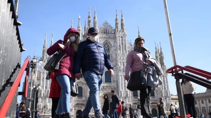 Passanten in Mailand tragen Mundschutz und gehen in eine U-Bahn-Station vor der Kathedrale. (Foto)