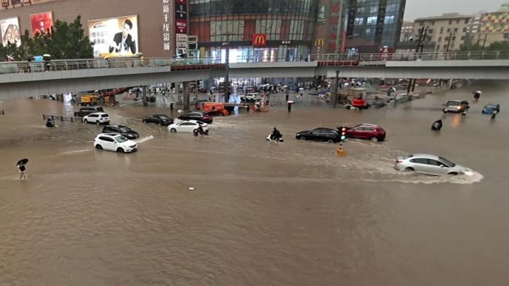 Fahrzeuge stehen in der zentralchinesischen Provinz Henan auf einer überfluteten Straße. (Foto)