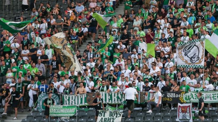 Mit Fahnen und Jubel feuern die Fans des VfL Wolfsburg ihren Verein an. (Symbolbild) (Foto)