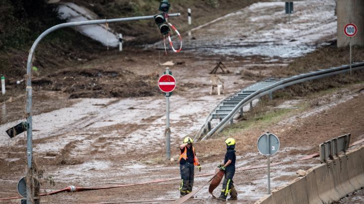 Feuerwehrmänner ziehen einen Schlauch über die verschlammte Bundesstraße 265. (Foto)
