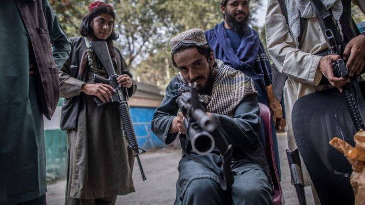 Aufnahme entstand im September: Ein junger Taliban-Kämpfer zielt zum Spaß mit seinem Gewehr in Richtung Fotograf, während er vor einer Polizeistation in Kabul Wache hält. (Foto)