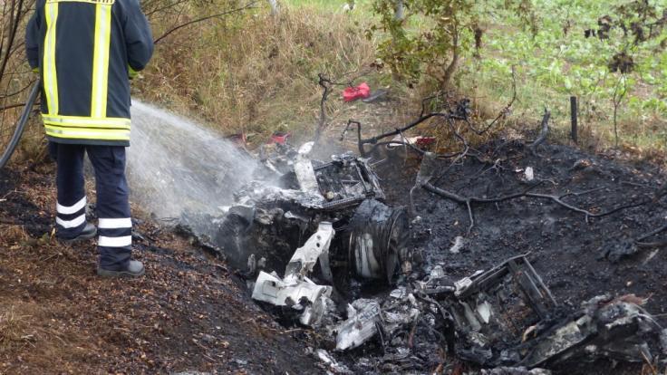 Ein Feuerwehrmann löscht die Überreste des ausgebrannten Ferraris bei Walsrode. (Foto)