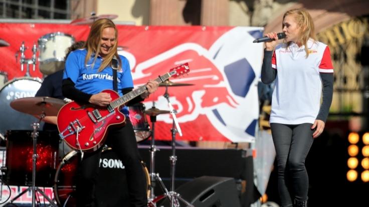 Silly (hier Sängerin Anna Loos im Union-Berlin-Shirt und Gitarrist Uwe Hassbecker im Hansa-Rostock-Trikot) traten bei der Aufstiegsfeier von RB Leipzig in Fan-Outfits anderer Vereine auf.