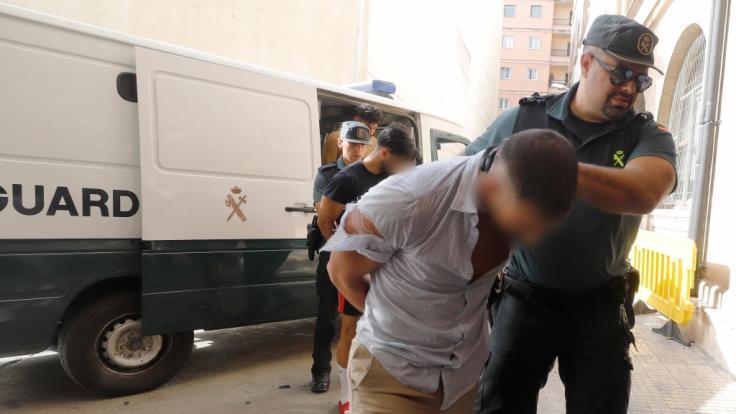 Einer der Tatverdächtigen wird von der Guardia Civil ins Gericht geführt.