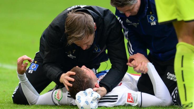 Hamburgs Spieler Jordan Beyer wird verletzt auf dem Platz versorgt. (Foto)