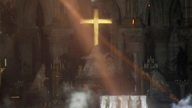 Der Altar der Kathedrale Notre-Dame ist am 15.04.2019 bei einem verheerenden Feuer von Rauch umgeben (oben) und der damalige Erzbischof von Paris, Andre Vingt-Trois, bei einer Messe in der Kathedrale 2015.