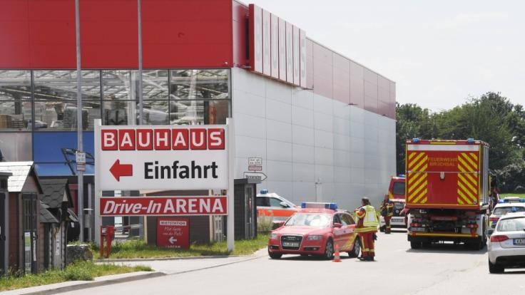 An einem Bauhaus Baumarkt stehen Einsatzfahrzeuge der Feuerwehr. Ein Kleinflugzeug ist gegen die Fassade des Gebäudes geprallt. Nach ersten Erkenntnissen der Polizei hat es bei dem Absturz am Samstag drei Tote gegeben. (Foto)