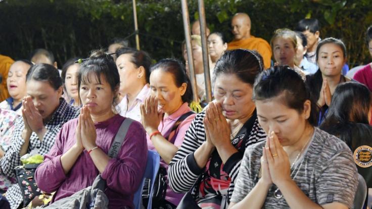 Mehrere Frauen beten in der Nähe der Höhle, in der eine Gruppe Jugendfußballer und ihre Trainer gefangen waren. (Foto)