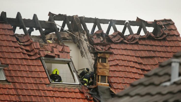 Feuerwehrleute suchen in einem beschädigten Wohnhaus nach Spuren. Bei dem Absturz eines Ultraleichtflugzeugs auf das Mehrfamilienhaus im niederrheinischen Wesel sind am Samstag drei Menschen gestorben.
