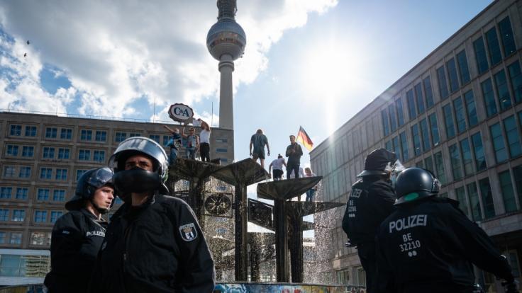 """Menschen sind bei einer Demonstration am 9. Mai 2020 auf dem Alexanderplatz auf den Springbrunnen """"Brunnen der Völkerfreundschaft"""" geklettert. (Foto)"""
