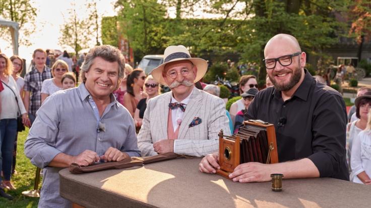 """""""Bares für Rares - Deutschlands größte Trödelshow"""": Andy Borg und Horst Lichter stehen am Expertisentisch von Sven Deutschmanek. (Foto)"""