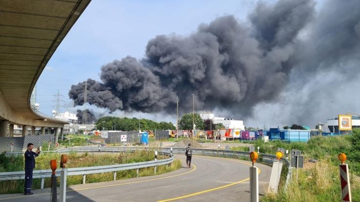 Eine dunkle Rauchwolke steigt über dem Chemiepark Leverkusen auf. Einsatzkräfte der Werkfeuerwehr sind im Einsatz. (Foto)