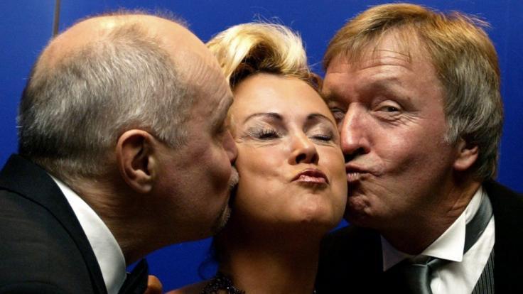 Marijke Amado wird geküsst von ihren Kollegen Thomas Koschwitz (l.) und Werner Schulze-Erdel (r.). (Foto)