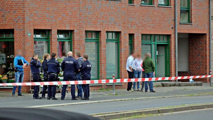 Polizisten und Passanten stehen vor einem Haus in der Innenstadt von Neuss. Nach Schüssen ist eine 27-jährige Frau gestorben.