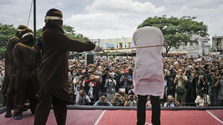 Ein mit Kapuze verhüllter Mann verteilt Peitschenhiebe. (Foto)