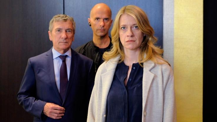 Davids Chef Hagedorn (Rudolf Kowalski, li.) und Michael (Christoph Maria Herbst) scheinen etwas vor Claire (Caroline Peters) verbergen zu wollen. (Foto)